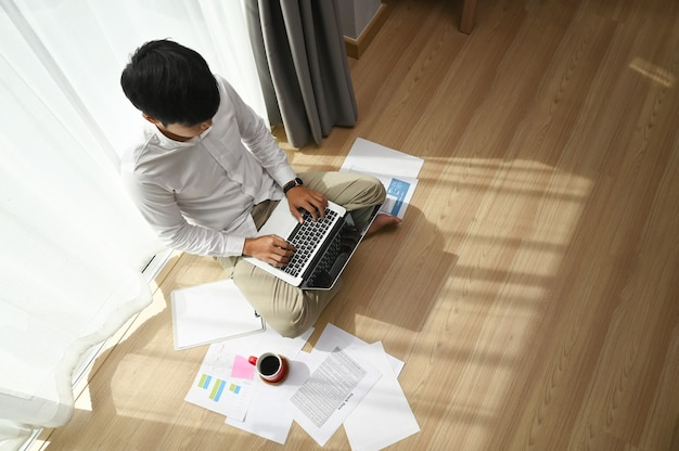 Overhead view of young man freelancer using laptop while sitting next to the window at home .