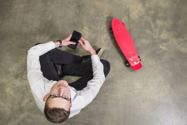 An overhead view of a young man holding mobile in hand looking up sitting near the red skateboard