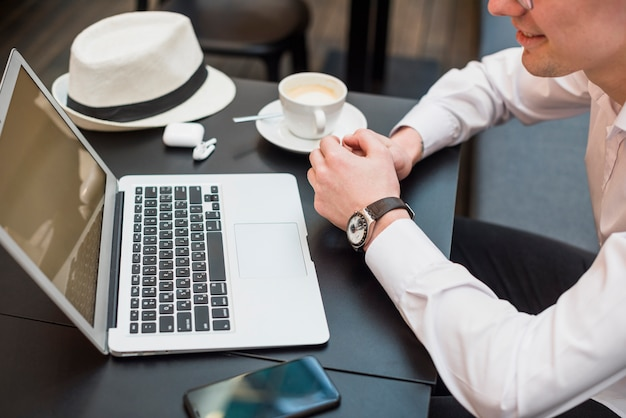 An overhead view of a young man looking at laptop with coffee; hat and mobile phone on table