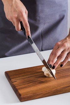An overhead view of a young woman cutting the knife with mushroom on wooden chopping board