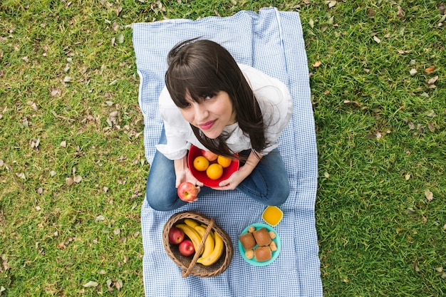 An overhead view of a young woman with fruits at picnic in the park