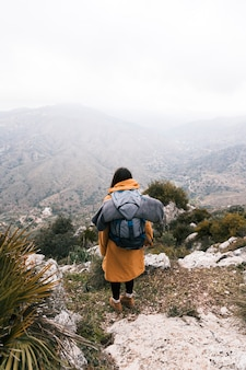 An overhead view of a young woman with her backpack overlooking the mountain