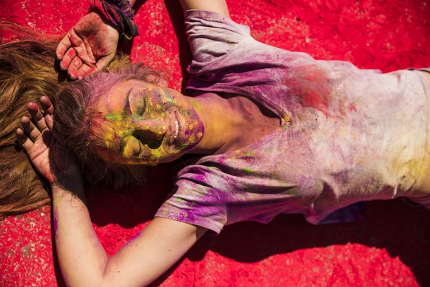 An overhead view of young women lying on red holi powder