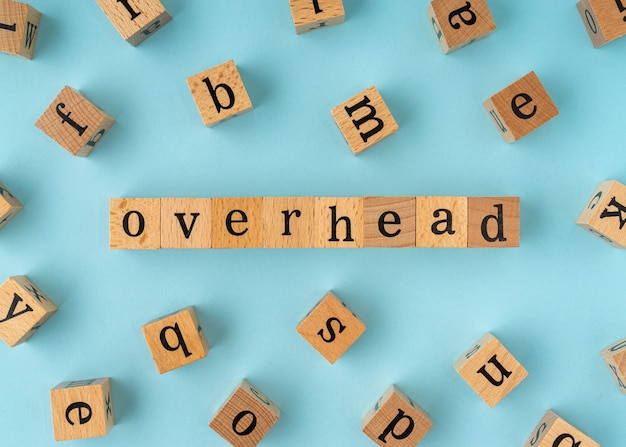 Overhead word on wooden block. flat lay view on blue background.