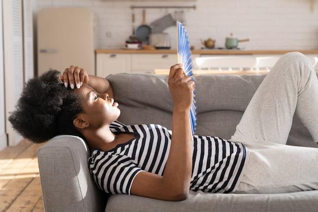 Перегретая африканская женщина, лежащая на диване, использует бумажный вентилятор, чтобы охладить воздух, страдает от высокой температуры внутри