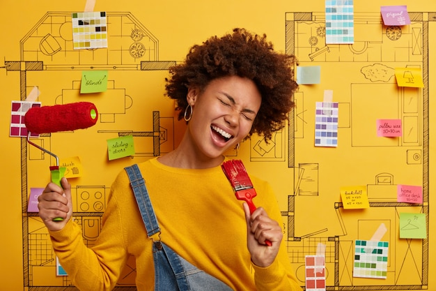Overjoyed african american woman holds paint brush as microphone, has fun after painting, wears yellow sweater, poses against house design project, busy repairing apartment, tilts head and laughs