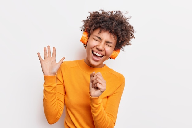 Overjoyed african american woman keeps palm raised has carefree expression sings song listens music in headphones wears casual orange jumper isolated over white wall. fun entertainment