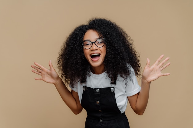 Overjoyed african american woman laughs out, raises palms, being in high spirit