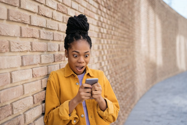 Overjoyed african american woman playing mobile game copy space excited female shopping online