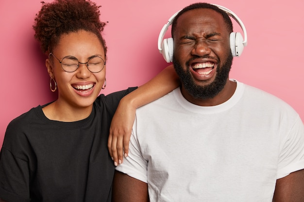 Overjoyed afro american couple have fun, listen favorite music in headphones, giggle over something positive, wear black and white clothes, enjoy spending time together, isolated on pink wall