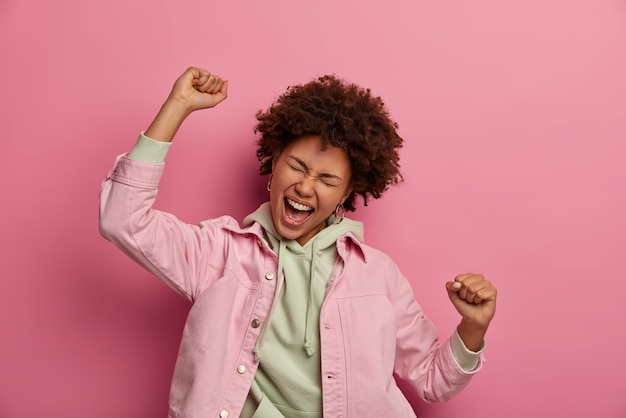 기뻐하는 아프리카 계 미국인 학생이 승리의 춤을 추고, 행복하게 외치며, 클라우드 9에 있고, 성공을 거두고, 재킷과 함께 까마귀를 입습니다.