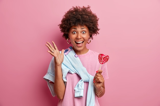 Overjoyed afro american teenage girl glad to be in merry company, raises hand, holds sweet candy, wears sweater tied over shoulder, smiles broadly,