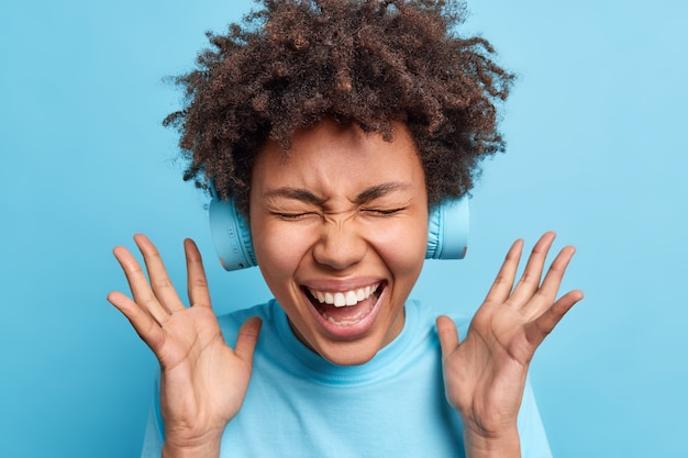Overjoyed afro american woman keeps hands raised exclaims joyfully closes eyes from happiness reacts on awesome news wears wireless headphones on ears isolated over blue wall. joy concept