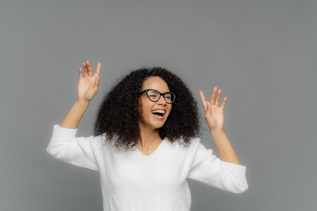 Overjoyed afro american woman raises hands, laughs happily, enjoys pleasant music
