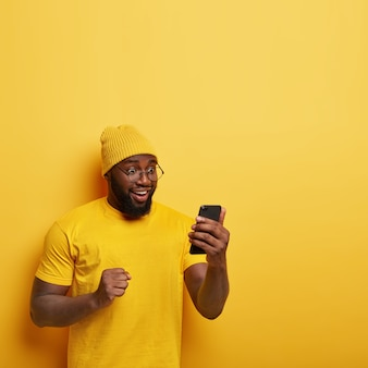 Overjoyed afro man with thick bristle, looks happily at cell phone, feels upbeat, celebrates good news, keeps clenched fist, wears yellow stylish hat