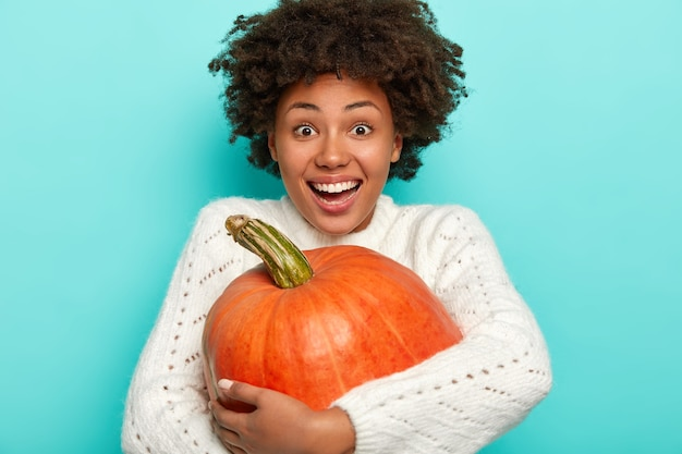 Overjoyed afro woman embraces big squash, smiles broadly, happy to harvest autumn crops, wears knitted white sweater