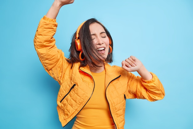Overjoyed asian girl moves actively dances carefree keeps arms raised enjoys awesome sound quality via headphones listens music has dark hair floating on wind wears orange jacket