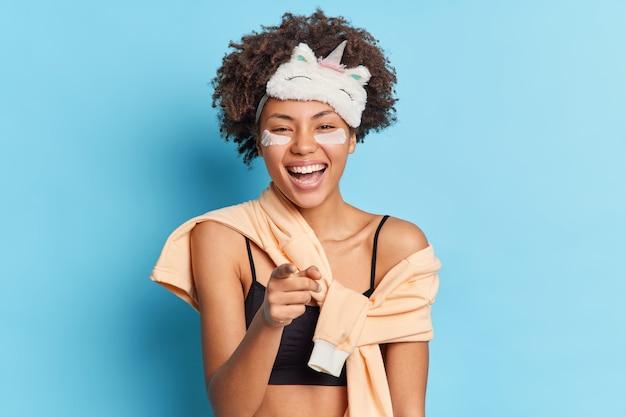 大喜びの魅力的な女性の笑顔は、寝間着に身を包んだパジャマに身を包んだカメラに直接人差し指を向けて喜んで青い壁に孤立した前向きな感情を表現します