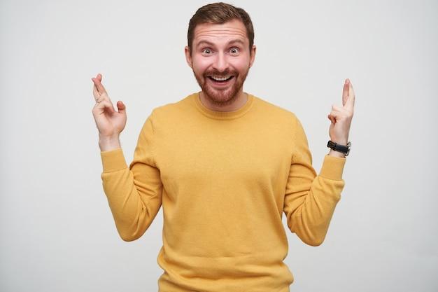 茶色の短い髪の魅力的な若いひげを生やした男は、広い目と口を開いて、幸運のために指を交差させて立っています。