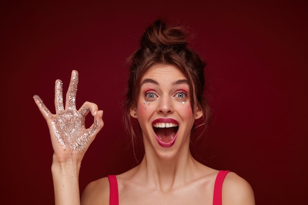 Overjoyed attractive young brunette woman wearing her hair in knot and having silver stars on her face, applying evening makeup before going out and raising ok gesture