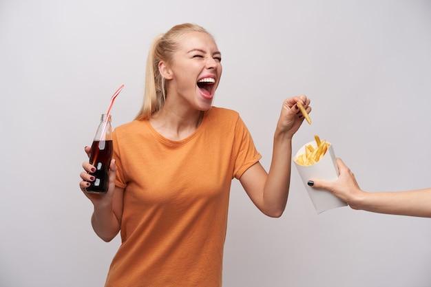 Giovane donna bionda dai capelli lunghi attraente felicissima in abiti casual che ride allegramente mentre prende patatine fritte da imballaggi di carta e tiene la bottiglia di soda, isolato su sfondo bianco
