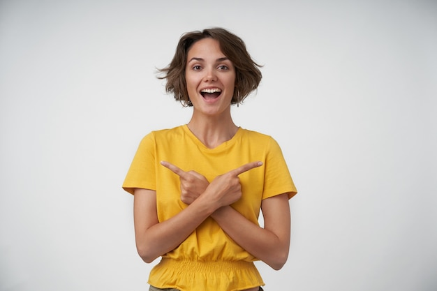 黄色のtシャツに立って、さまざまな方向に人差し指を指して、広い笑顔で幸せそうに見える短い茶色の髪を持つ大喜びの魅力的な若い女性