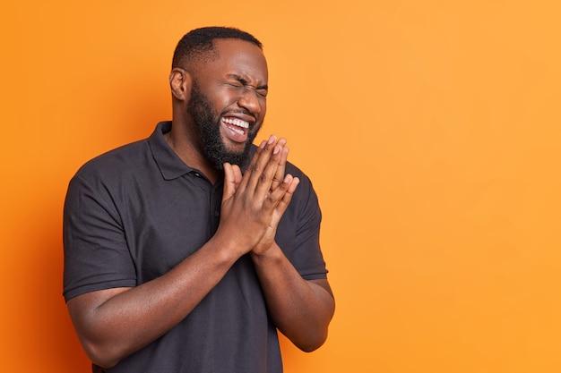 기쁜 수염 난 성인 남자가 손바닥을 문지르고 캐주얼 한 검은 색 티셔츠를 입고 행복하게 웃으며 텍스트 복사 공간이있는 밝은 주황색 벽에 재미있는 농담 포즈를 듣는다.