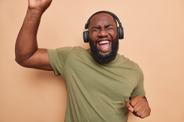 Overjoyed bearded black man dances carefree keeps arms raised up moves with rhythm of music listens music via headphones dressed in casual t shirt isolated over brown wall