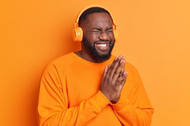 Обрадованный бородатый чернокожий мужчина держит ладони вместе, широко улыбается, имеет белоснежные зубы, слушает любимый плейлист через беспроводные наушники, одетый в ярко-оранжевый джемпер позирует в помещении