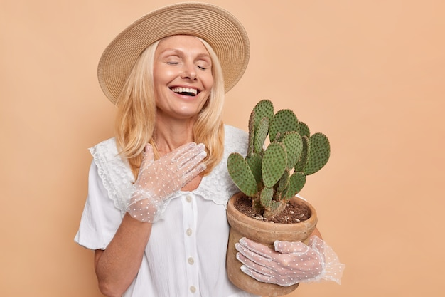 Overjoyed beautiful woman with fair hair laughs happily keeps eyes closed wears white dress lacy gloves hat carries pot of green succulent cactus isolated over beige wall