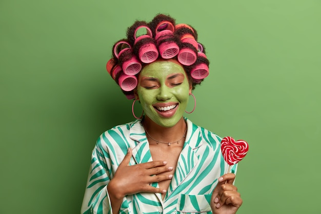Overjoyed beautiful woman with hair curlers and green facial mask, laughs happily, has fun during beauty procedures at home, holds lillopop on stick, prepares for party. skin pampering, wellness, spa