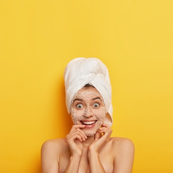 Overjoyed beautiful woman with toothy broad smile, has facial treatments, applies scrub mask for cleansing skin, has happy expression