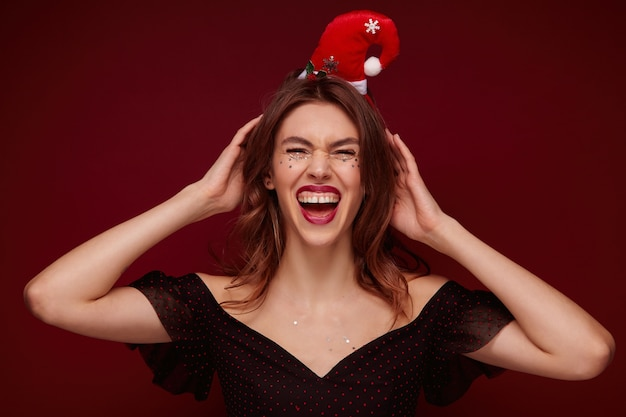 Overjoyed beautiful young brunette female dressed in festive clothes wearing santa hat and holding hands on her head, laughing happily and demonstrating her white perfect teeth