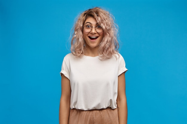 Overjoyed beautiful young woman wearing white oversize t-shirt and round eyeglasses happy to receive unexpected positive news, opening mouth widely
