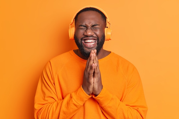 大喜びの黒ひげを生やした大人の男は手のひらを一緒に押し続けて明るいスタジオの壁に隔離されたオレンジ色のセーターに身を包んだステレオヘッドフォンを身に着けている面白いものに明るい気分で笑う