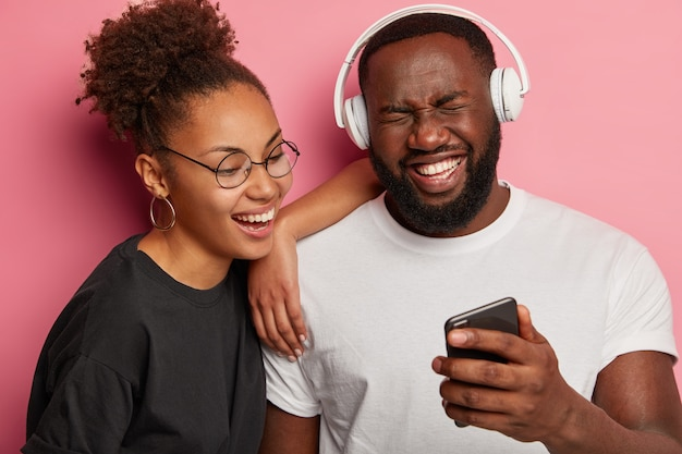 Overjoyed black hipster guy holds smartphone, laughs happily as watch funny movie on smartphone together with girlfriend, use stereo headphones.