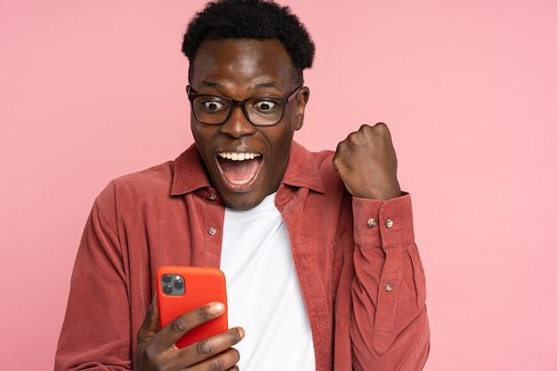 Overjoyed black male look at smartphone, smile feel joyful reading good news, doing winner gesture