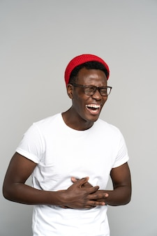 Overjoyed black millennial man shows her broad smile, holding his stomach from laughter. studio.