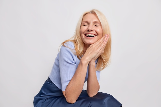 Overjoyed blonde fifty years old woman smiles broadly keeps palms pressed together expresses positive authentic emotions laughs at something dressed in stylish clothes isolated over white wall