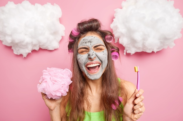 Overjoyed brunette european woman applies hair curlers poses with bath sponge and toothbrush isolated over pink wall with white clouds above