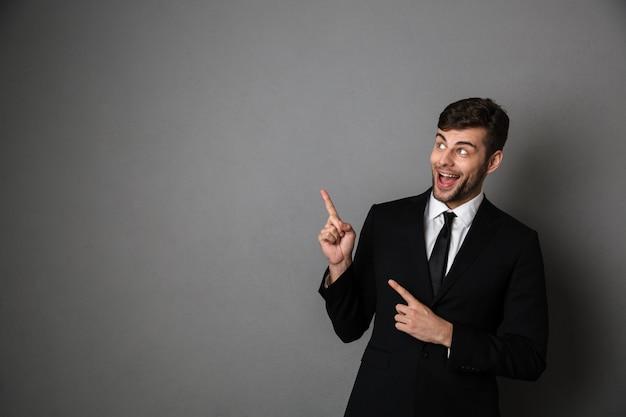 よそ見2本の指で指している古典的なスーツで大喜びのブルネット男