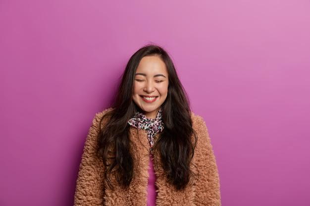 健康な肌、心から笑顔、茶色のコートを着て、目を閉じて、ライラックのスタジオの壁に隔離され、楽しんで、写真のポーズをとる大喜びのブルネットの女性。人