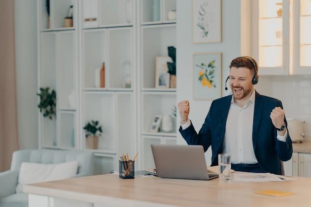 Довольный бизнес-профессионал, добивающийся успеха, поднимающий кулаки и кричащий от счастья, используя ноутбук и гарнитуру, сидя на своем рабочем месте дома или в офисе