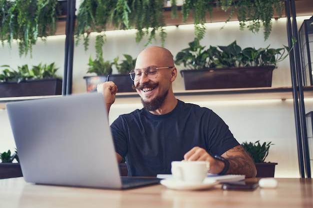 기뻐하는 사업가나 학생이 카페에서 노트북을 사용하는 동안 노트북 화면을 보는 동안 예 제스처를 보여줍니다