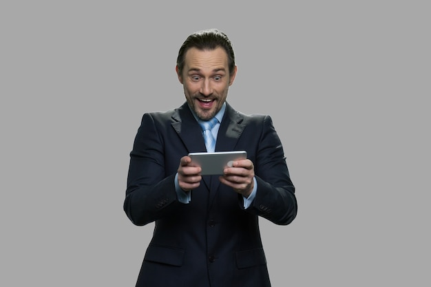 스마트 폰을 사용하여 기뻐 사업가. 회색 바탕에 온라인 게임을 즐기는 사업가. 비즈니스 사람, 기술 및 재미.