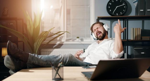 Обрадованный бизнесмен с ногами на столе, слушающий музыку в наушниках, делая вид, что играет на гитаре в офисе