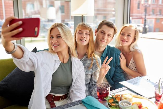 함께 카페에서 사진을 위해 포즈를 취하는 기뻐 백인 사람들