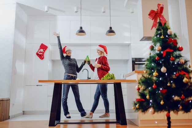 Overjoyed caucasian senior woman and her daughter toasting with beer in kitchen on christmas eve. both having santa hats on head. on kitchen counter there are vegetables.