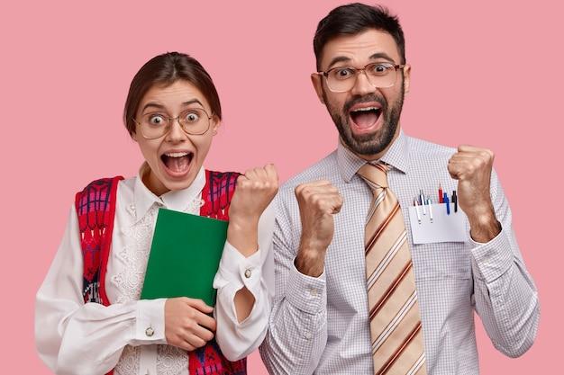 La donna goffa e l'uomo nerd felicissimi stringono i pugni, festeggiano la fine della preparazione per il seminario, indossano occhiali, vestiti eleganti vecchi, portano libri di testo