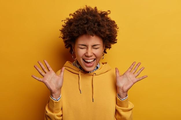 大喜びの巻き毛の民族女性が手のひらを上げ、前向きに笑う